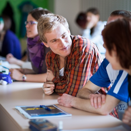 young, handsome college student sitting in a classroom full of students during class Stock Photo - 11303395