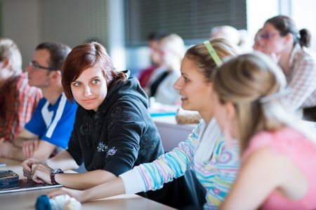 higher learning: young, pretty female college student sitting in a classroom full of students during class (shallow DOF; color toned image) Stock Photo
