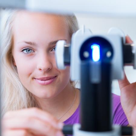 oculist: concepto de optometría - paciente bonita, joven mujer con los ojos examinados por un oftalmólogo (imagen a color entonado, someras DOF)