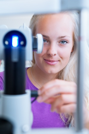 examined: optometry concept - pretty, young female patient having her eyes examined by an eye doctor (color toned image; shallow DOF) Stock Photo