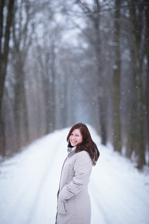 Enjoying the first snow: young woman outdoors on a lovely forest path watching the snowflakes falling (color toned image) photo