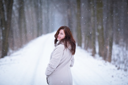 coutryside: Enjoying the first snow: young woman outdoors on a lovely forest path watching the snowflakes falling (color toned image)