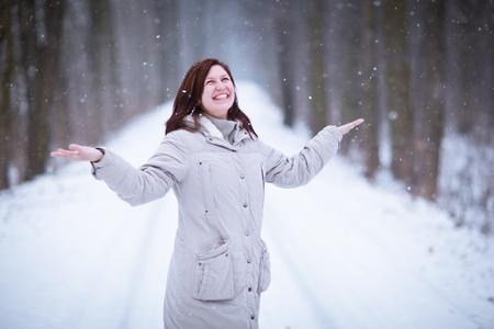 mujeres maduras: Disfrutar de la nieve en primer lugar: al aire libre joven mujer en un camino hermoso bosque viendo los copos de nieve cayendo (imagen a color entonado)