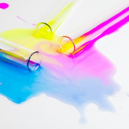 sustancias toxicas: tubos de ensayo con sustancias de colores derramados sobre una mesa blanca en un laboratorio Foto de archivo