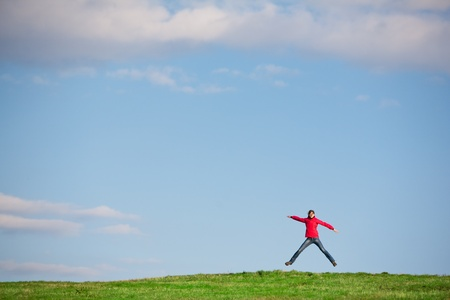 Young woman jumping for joy against blue sky in the middle of a green field photo