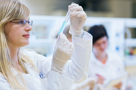 laboratory technician: portrait of a female researcher carrying out research in a chemistry lab (color toned image; shallow DOF)