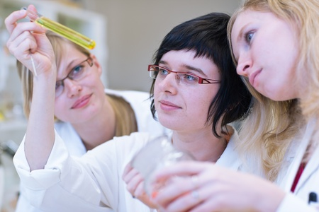 thre female researchers carrying out research in a chemistry lab (color toned image; shallow DOF) photo