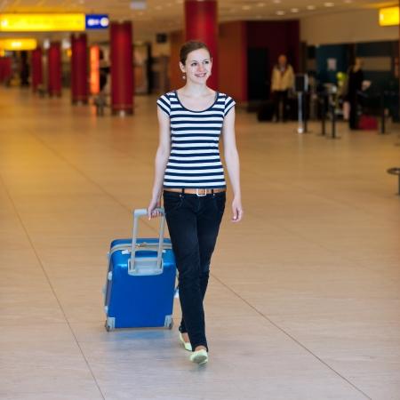 Mooie jonge vrouwelijke passagier op de luchthaven (ondiepe DOF; kleur getinte afbeelding)