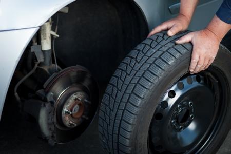 mecánico de cambiar una rueda de un coche moderno (imagen a color entonado) Foto de archivo