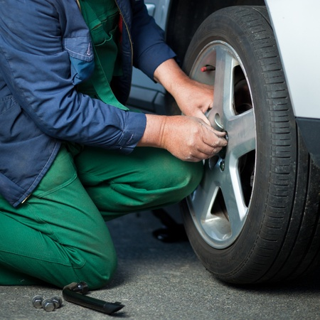 mechanic changing a wheel of a modern car (color toned image) Stock Photo - 11303612