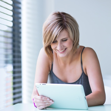 Pretty, young businesswoman/college student using her tablet computer (shallow DOF; color toned image) Stock Photo - 11303454