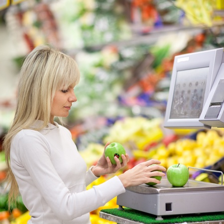produce sections: Beautiful young woman shopping for fruits and vegetables in produce department of a grocery storesupermarket (shallow DOF) Stock Photo