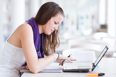 pretty female college student studying in the university library/study room  Stock Photo - 11527004