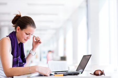 pretty female college student studying in the university library/study room Stock Photo - 11527024