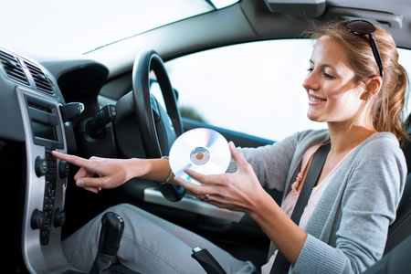 woman listening to music: Young female driver playing music in the car (changing CDs)