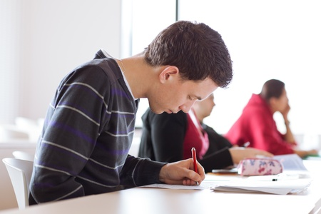 young, handsome male college student sitting in a classroom full of students during class Stock Photo - 11527029