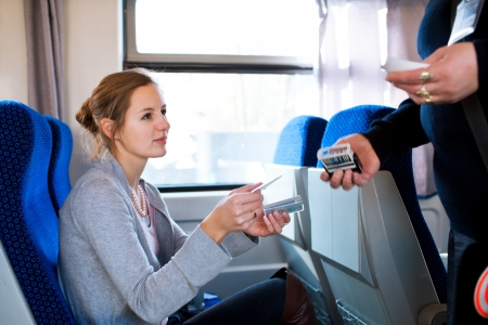 conductors: Young woman traveling by train, having her ticket checked by the train conductor