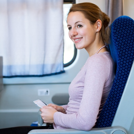 Young woman traveling by train, holding her train ticket , smiling photo