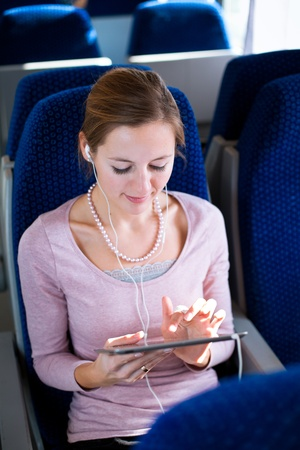 Young woman using her tablet computer while traveling by train Stock Photo - 11762070