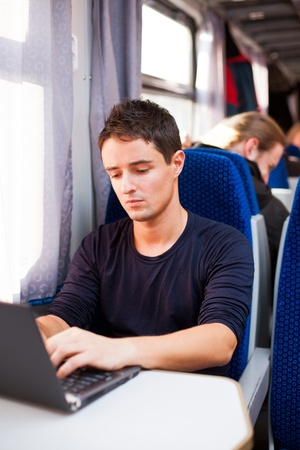 Handsome young man using his laptop computer while on the train (shallow DOF; color toned image) photo