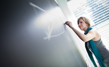 college classroom: pretty young college studentyoung teacher writing on the chalkboardblackboard during a math class (color toned image; shallow DOF) Stock Photo