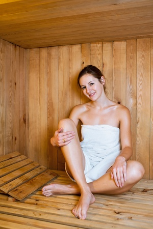 Young woman relaxing in a sauna photo