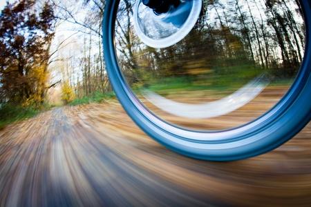 Fahrrad fahren in einem Stadtpark auf einem schönen Herbst / Herbst Tag (Motion Blur wird verwendet, um Bewegung zu vermitteln) Standard-Bild