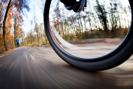 ciclista: Montar en bicicleta en un parque de la ciudad en un hermoso oto�o  d�a de oto�o (desenfoque de movimiento se utiliza para transmitir el movimiento)