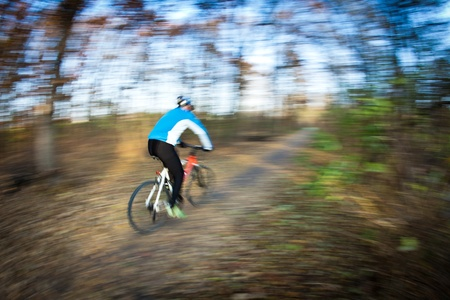 convey: Bicycle riding in a city park on a lovely autumnfall day (motion blur is used to convey movement)