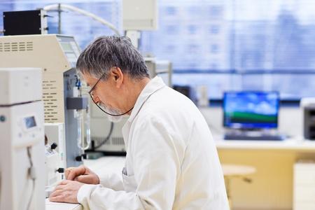 investigaci�n: investigador senior masculino llevar a cabo la investigaci�n cient�fica en un laboratorio (DOF, imagen en color entonado) Foto de archivo