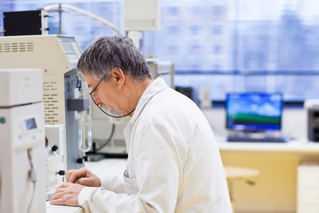 health care research: senior male researcher carrying out scientific research in a lab (shallow DOF; color toned image)
