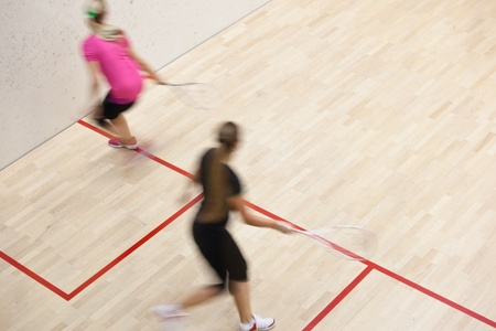 squash: Two female squash players in fast action on a squash court (motion blurred image; color toned image)