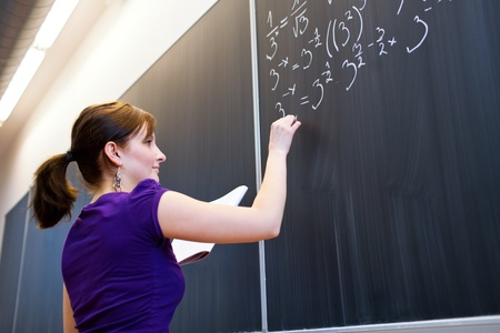 high school teacher: pretty young college student writing on the chalkboardblackboard during a math class (color toned image; shallow DOF)