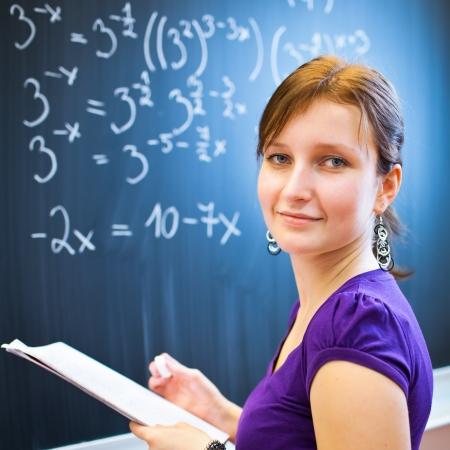 matematica: bastante joven estudiante universitario por escrito en la pizarra  la pizarra durante una clase de matem�ticas (imagen a color entonado, DOF bajo) Foto de archivo
