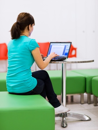 Pretty young female student with laptop on college/university campus Stock Photo - 11761918