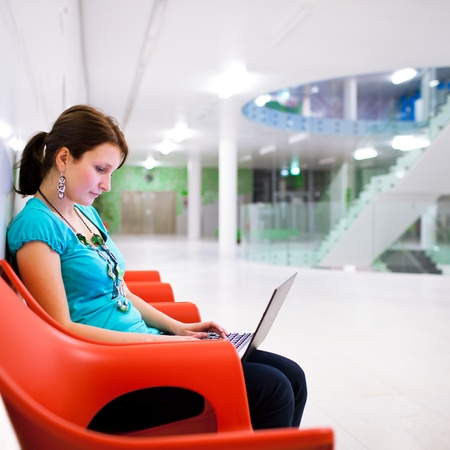 Pretty young female student with laptop on college/university campus Stock Photo - 11762025