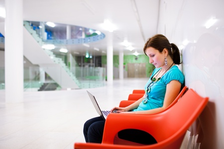 Pretty young female student with laptop on college/university campus Stock Photo - 11761919