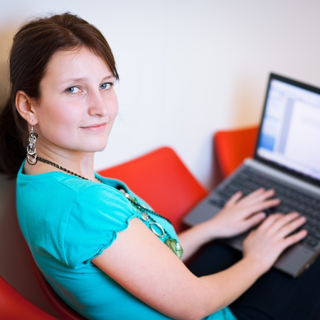 adult classroom: Pretty young female student with laptop on collegeuniversity campus Stock Photo