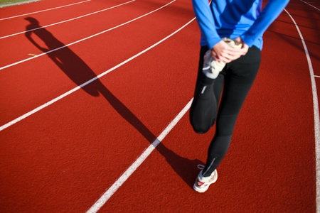 Young woman stretching before her run casts a shadow on the track photo