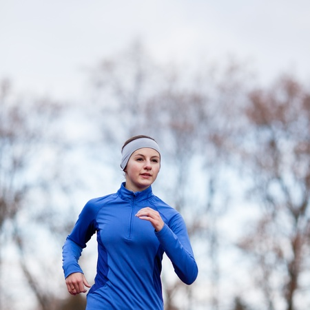 Portrait of a woman running against against blue sky photo