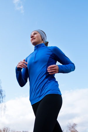 ジョグ: 青い空を背景に対して走っている女性の肖像画