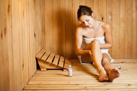 Young woman relaxing in a sauna photo
