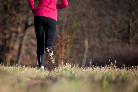 Jogging outdoors in a meadow (shallow dof, focus on the running shoe) Stock Photo - 11940449