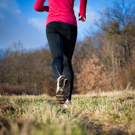 Jogging outdoors in a meadow (shallow dof, focus on the running shoe) Stock Photo - 11976577