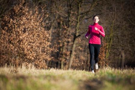 atleta corriendo: Mujer joven correr al aire libre en una bonita y soleada de invierno  oto�o d�a (movimiento de la imagen borrosa)
