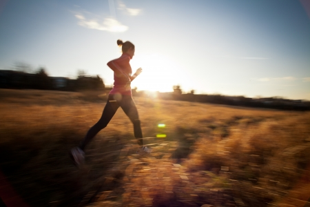 woman jogging: Young woman running outdoors on a lovely sunny winterfall day (motion blurred image)