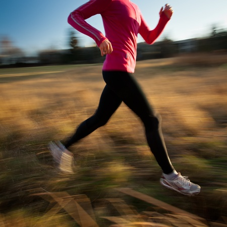 Young woman running outdoors in a city park on a cold fall/winter day (motion blurred image) Stock Photo - 11940462