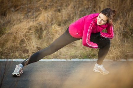 Young woman stretching before her run outdoors on a cold fallwinter day