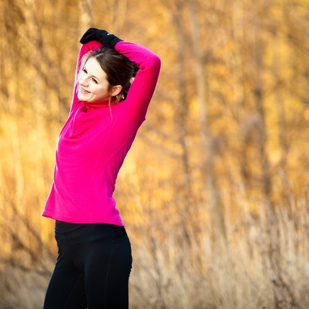 Young woman stretching before her run outdoors on a cold fall/winter day photo