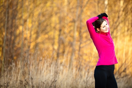 Young woman stretching before her run outdoors on a cold fallwinter day photo
